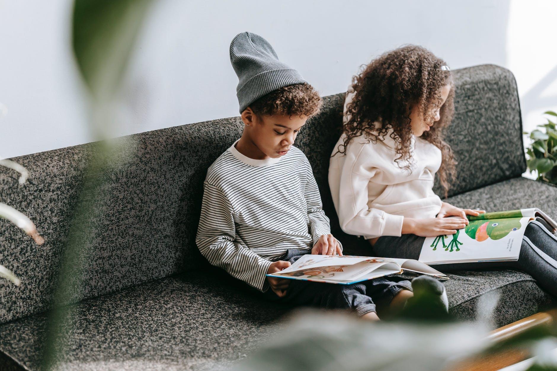 focused black children reading books with bright illustrations